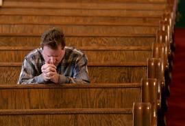 Man praying alone in church pews