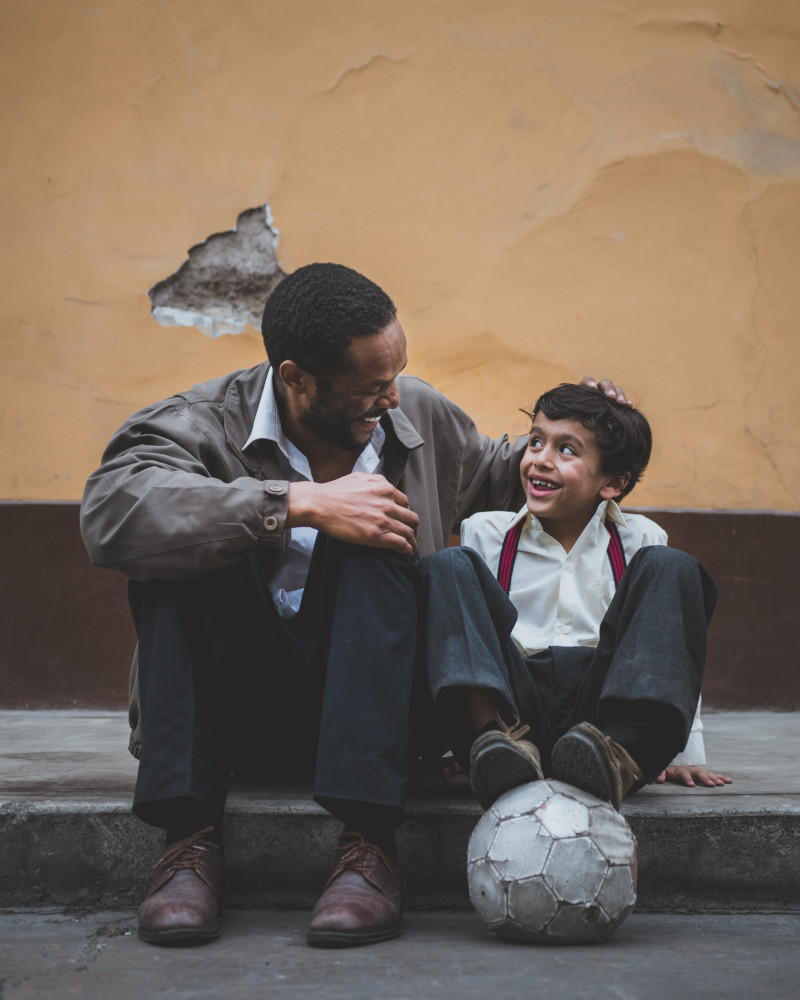 Photo of man with child by Sebastián León Prado on Unsplash
